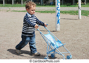 little boy and girl playing with baby carriages.