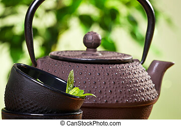 Kettle and closeup fresh mint leaves in a tea cup