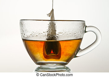 Teabag in a cup filled with hot water isolated on white...