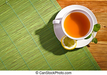 Hot tea with fresh leaves and lemon on bamboo mat