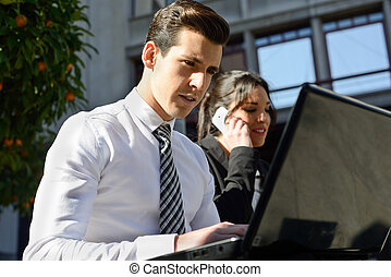 Portrait of attractive young businessman typing in a laptop...