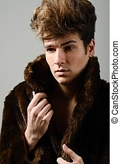 Attractive young man wearing fur coat with modern hairstyle...
