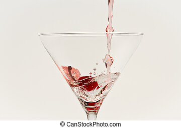 Red drink pouring down into grass with cherry isolated on white background