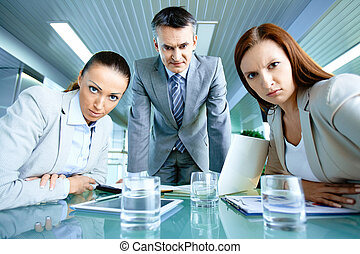 Displeasure - Serious boss with his two employees looking at...