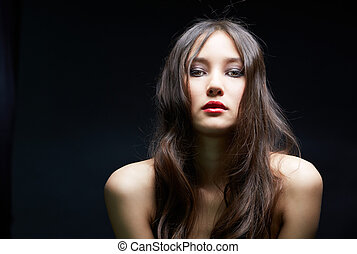 Gorgeous female - Young woman looking at camera over black...