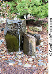 A rocky bubbling water fountain in a courtyard garden