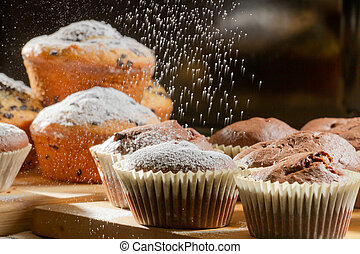 Falling caster sugar on various muffins