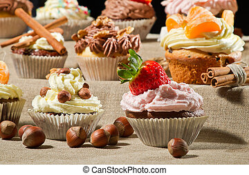 Various muffins with cream, fruits and nuts
