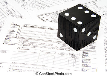Taxes - A giant die on a stack of tax forms.