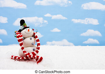 Merry Christmas - Snowman wearing scarf on sky background,...