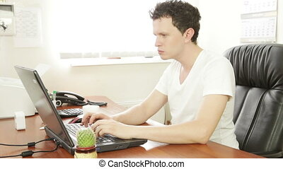 Young man behind the laptop