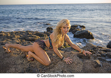 Woman in colorful outfit crawling on Rocks