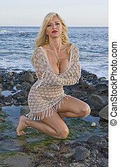 Blond Woman in Lace dress kneeling on Rocks at the Beach