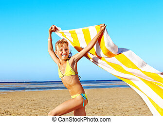 Child running at beach with towel.
