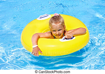Child  on inflatable ring in swimming pool.