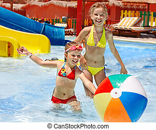 Children swimming in pool - Little girl playing ball in...