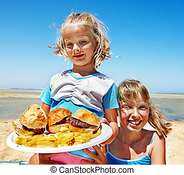 Child eating fast food - Child eating fast food at beach...