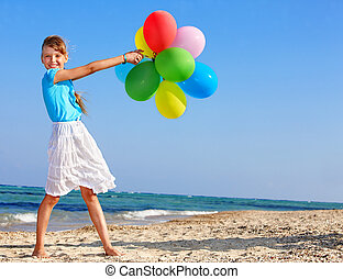 Child playing with balloons at the beach - little girl...