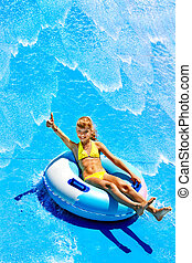 Child on water slide at aquapark Summer holiday