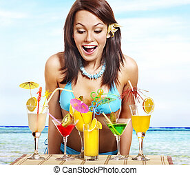 Girl in bikini on beach drinking cocktail - Young woman in...