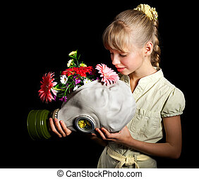 Child holding flowers and gas mask .