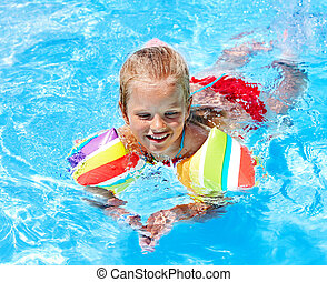 Child with armbands in swimming pool Summer outdoor