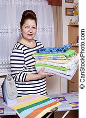 Elderly woman ironing towels at home