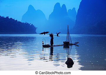 YANGSHUO - JUNE 19: Chinese man fishing with cormorants birds in Yangshuo, Guangxi region, traditional fishing use trained cormorants to fish, June 19, 2012 Yangshuo in Guangxi, China