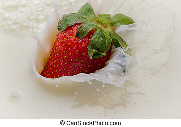 Strawberry falling into milk with a splash