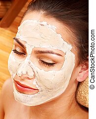 Young woman having clay facial mask - Beautiful girl having...