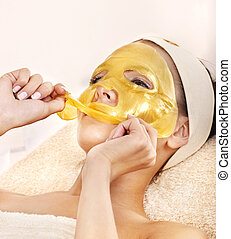 Girl with gold facial mask.