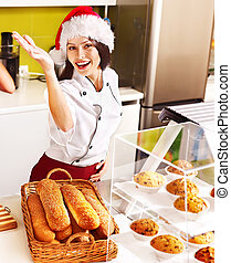 Female chef in Santa hat holding food. - Female chef in...