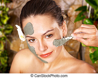 Young woman having clay body mask. - Beautiful girl having...