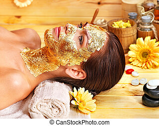 Woman getting facial mask . - Woman getting gold facial...