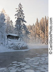 Hut near pond in winter forest - Small hut or log caping at...