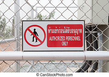 Authorized personnel only sign on a fence