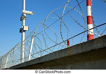 Security cameras and razor wire against a blue sky.