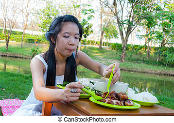 Asian Thai girl is eating beside swamp