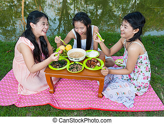 Asian Thai girls picnic together beside swamp