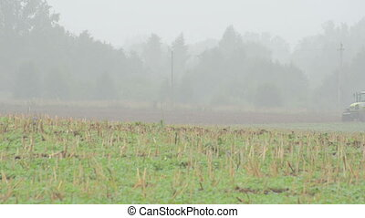 tractor plow field fog - tractor plow agriculture field in...