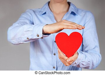 protecting a heart - a person holding and protecting a heart...