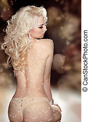 Back of slim blond woman wearing in twinkled crystals...