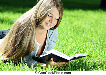 Young woman reading book on green grass - young woman in...