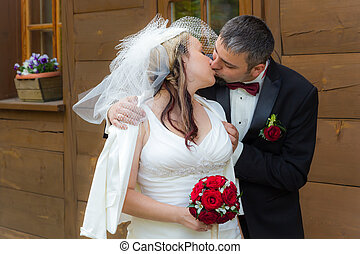 Young couple kissing in front of an vintage house