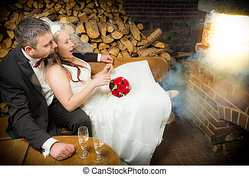 Surprised young couple sitting in front of a smoking fireplace