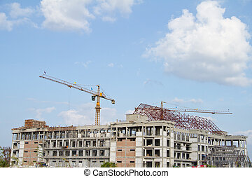 Crane and workers at construction site against blue sky...
