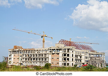 Crane and workers at construction site against blue sky....
