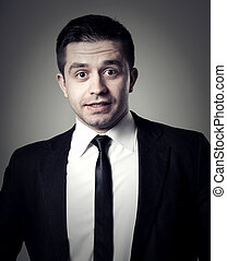 Young businessman with surprise expression on his face on a...