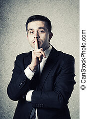 Business man with finger on lips asking for silence over...