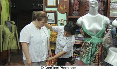 Woman tries on clothes at the tailor